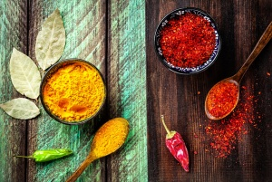 Chili, paprika, turmeric and bay leaves on wooden green and brown board background