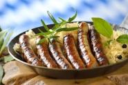 Leckere Rostbratwrste auf Sauerkraut in der Eisenpfanne serviert
