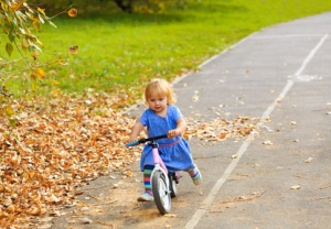 cute little girl riding runbike in autumn, kids sport