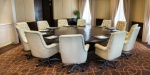interior of a boardroom - round table and white leather armchairs